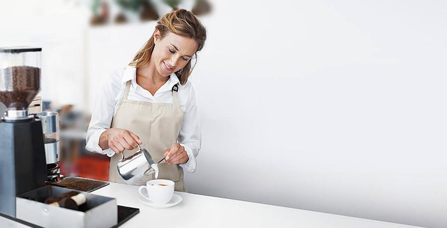 Frau steht an Kaffeemaschine und gießt sich einen Kaffee ein