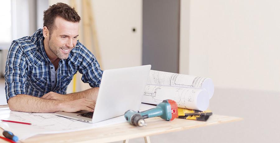 Mann sitzt vor Laptop an Werkbank
