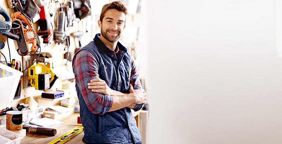 Mann lehnt stehend an Werkbank und lächelt