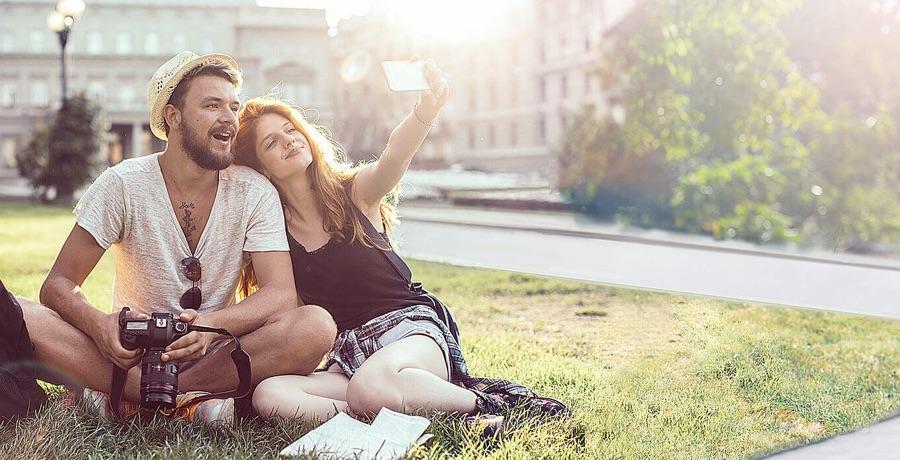 Junges Paar sitzt auf Parkwiese und macht ein Foto von sich